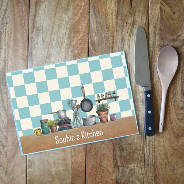 "A personalised chopping board with an illustration featuring kitchen items and the words ""Sophie's Kitchen"""