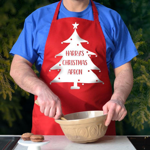 "A personalised red Christmas apron. the apron has a Christmas tree design printed on it and the words ""Harry's Christmas apron"""