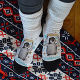 "A pair of personalised white socks with a penguin design and the words ""merry Christmas"" printed on them, the socks also have a custom name in light blue lettering."