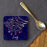 A personalised Christmas coaster on a table next to a tea spoon