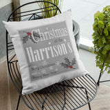 A personalised white, grey and red Christmas cushion with a text based design and holly leaf illustrations