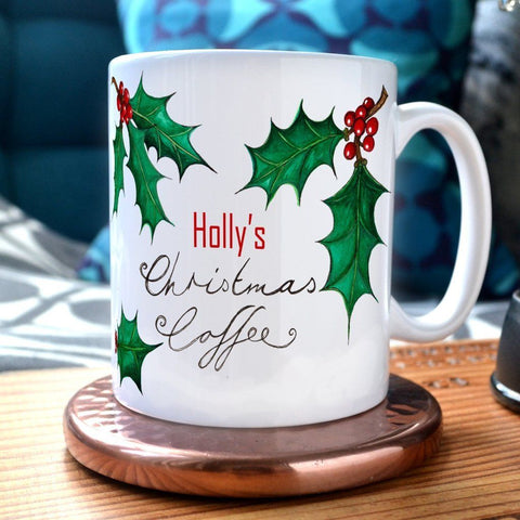 "A personalised Christmas mug with the message ""Holly's Christmas Coffee"" and illustrations of holly leaves printed onto it."