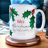 "A personalised Christmas mug with the message ""Holly's Christmas Hot Chocolate"" and illustrations of holly leaves printed onto it."