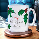 "A personalised Christmas mug with the message ""Holly's Christmas Tea"" and illustrations of holly leaves printed onto it."