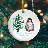"A personalised Christmas bauble with a penguin and a Christmas tree printed on it along with the message ""My first Christmas, Catherine 2019"""