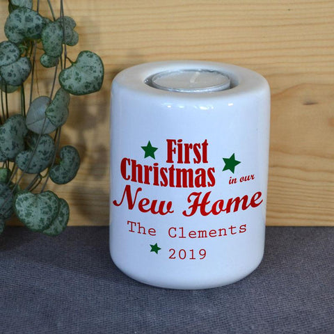 A personalised white ceramic candle holder with a message in red lettering and green stars.