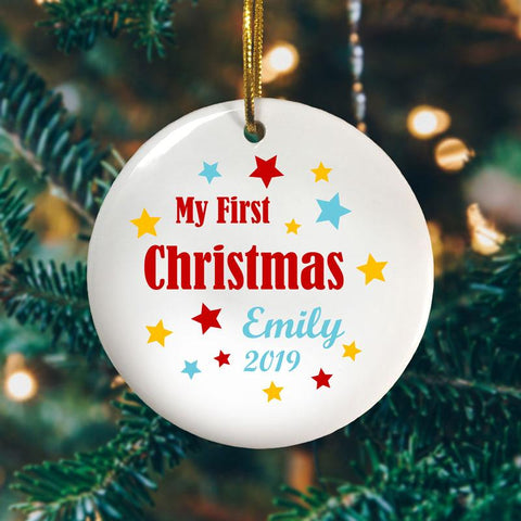A personalised Christmas decoration celebrating a baby's first Christmas. The design is text based with red, yellow and pale blue stars around the words.