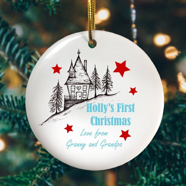 "A round ceramic Christmas decoration with an illustration of a house and the words ""Holly's First Christmas love Granny and Grandpa"""