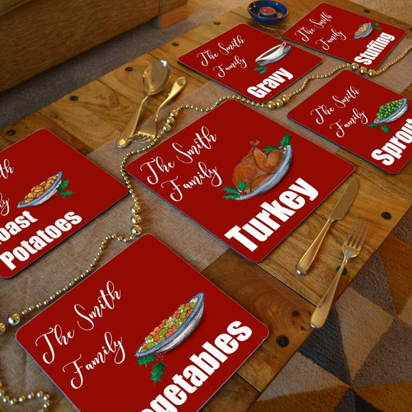 A dining table with personalised Christmas placemats on. The placemats are red with white text and illustrations of Christmas food