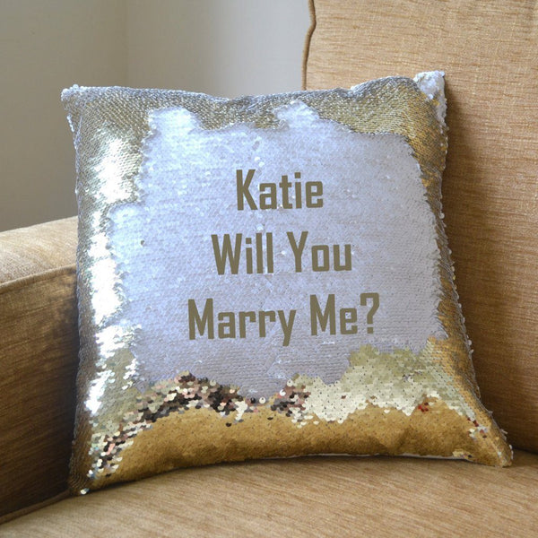 "A gold reveal cushion with the message ""Katie will you marry me?"""