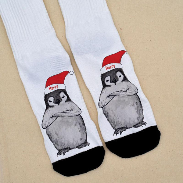 A pair of personalised socks with a grumpy Christmas penguin printed on them