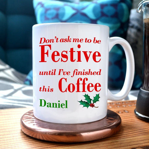 "A personalised Christmas mug with the text ""don't ask me to be festive until I've finished this coffee"" printed on it"