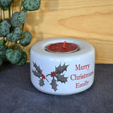 A personalised christmas candle holder in white with a holly leaf design and custom lettering in red.