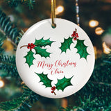 "A personalised white ceramic decoration. The decoration is printed with a holly pattern and has the words ""Merry Christmas Olivia"" in red lettering in the centre"