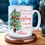 "A personalised mug with the words ""It's beginning to look a lot like Christmas"" printed on in a red italic font.  The mug also has an illustration of a Christmas tree and the name ""Aimee"" printed on it"