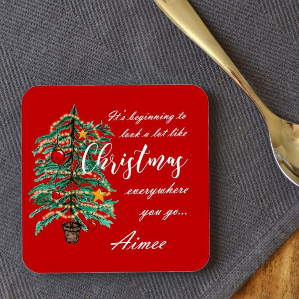 "A personalised red square coaster with an illustration of a Christmas tree and the words ""it's beginning to look a lot like Chrsitmas"" printed onto it. The coaster is customised with the name ""Aimee"""