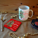 "A personalised Christmas mug and matching coaster with the words ""It's beginning to look a lot like Christmas, Aimee"" printed on them next to an illustration of a Christmas tree"
