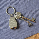 A personalised engraved bottle opener keyring on a table