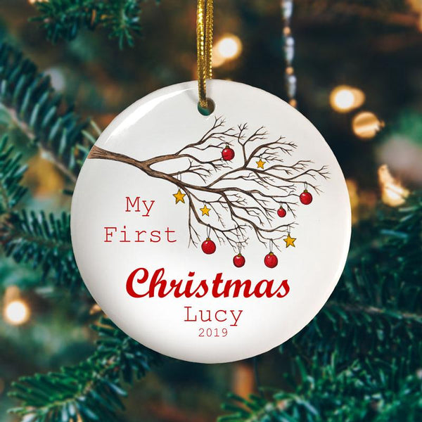 A personalised Christmas bauble celebrating a child's first Christmas. The design includes a winter tree decorated with gold stars and red baubles.