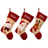 3 personalised Christmas stockings in a row. The stockings are made from natural calico and have red felt tops heals and toes. Each one has a character on, one with a Santa, one with a snowman and one with a reindeer. The stockings have an embroidered name at the top in white lettering.