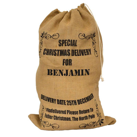 A personalised hessian Santa sack with black lettering in a postal service style design.