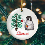 A personalised circular Christmas decoration with a penguin and Christmas tree image printed onto it
