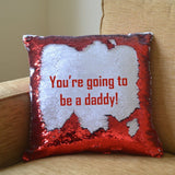 "A personalised red reveal cushion with the message ""you're going to be a daddy"" printed onto it"