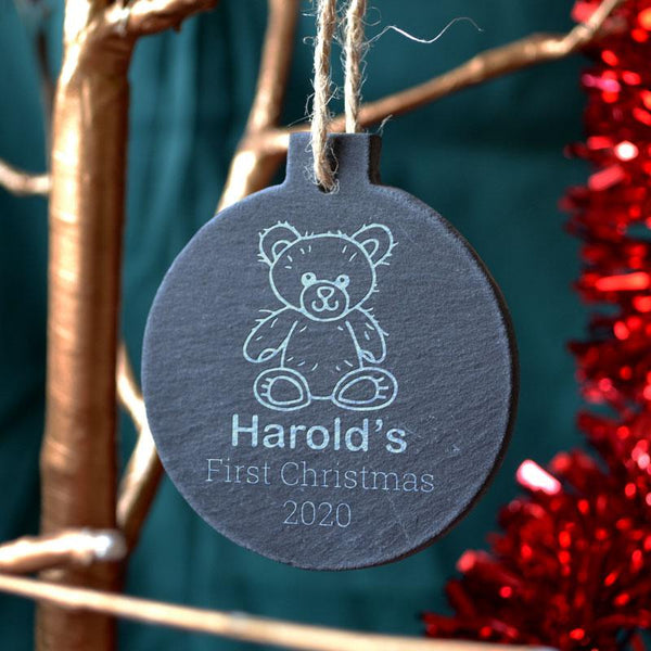 "A personalised round slate christmas bauble with an engraved design. The design features a teddy bear icon at the top and the words ""Harold's first Christmas 2020"" below."