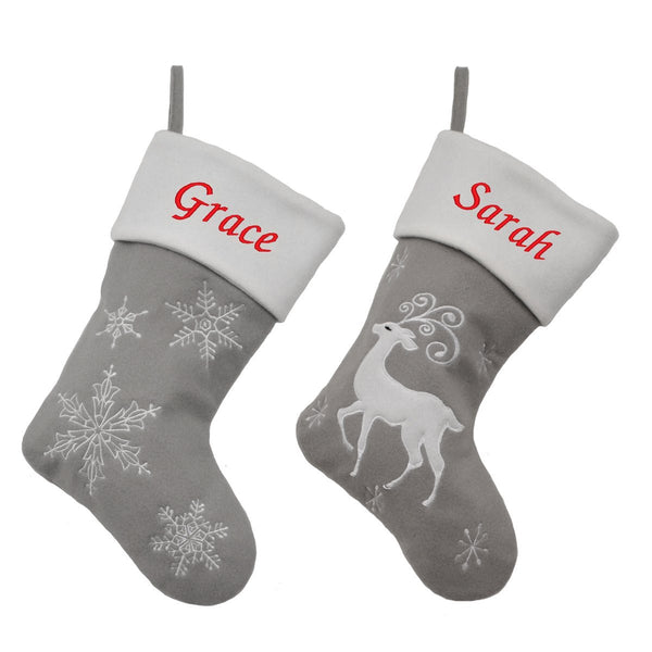 2 Christmas stockings in pale grey and white, one has a snowflake pattern and one has a stylised reindeer. Both are embroidered with a name in red on the white top of the stocking.