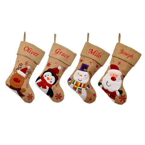 4 personalised hessian Christmas stockings, one with a penguin, one with Santa, one with a snowman and one with a reindeer. All the stockings have a christian name embroidered on the top of the stocking in red lettering.