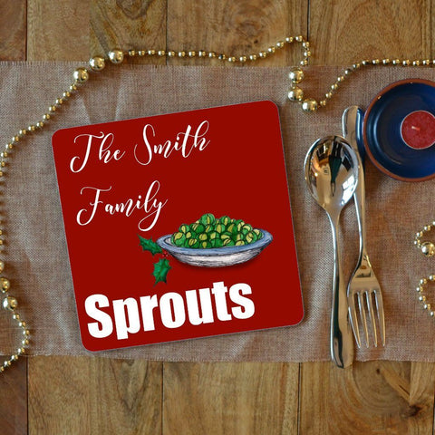 "a personalised sprouts Christmas placemat with white text which says ""the Smith family sprouts"" on a red background"