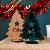Two personalised Christmas decoration cut in a tree shape. One is made from oak and one is made from green acrylic.
