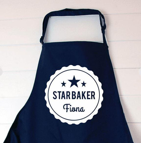 "A navy blue personalised apron with a white circular design printed on the front. The design features 3 stars at the top, and the words ""star baker Fiona"""