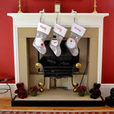 3 personalised Christmas stockings hanging on a fire place
