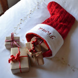 a personalised Christmas stocking on the end of a bed with presents inside