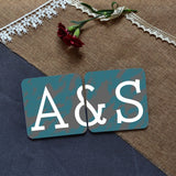 "a personalised coaster pair in teal and white. The coasters have lettering which reads ""A&S"" when placed next to each other"