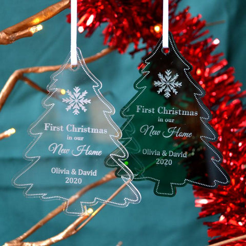 "Two personalised ""new home"" Christmas decorations in a tree shape. One is made from clear acrylic and one is made from green acrylic."
