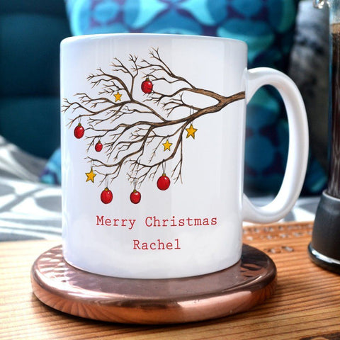 "A personalised Christmas mug with a winter tree decorated with red baubles and gold stars. The mug has the message ""Merry Christmas Rachel"" printed onto it"