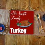 "A personalised Christmas placemat with a turkey illustration. the placemat has a red background with white text reading ""the Smith family turkey"""