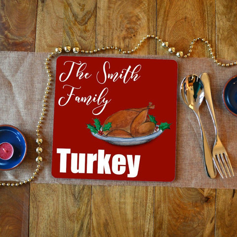"A personalised square placemat with the words ""the Smith family turkey"" in white lettering on a red background. The is an illustration of a Christmas turkey."