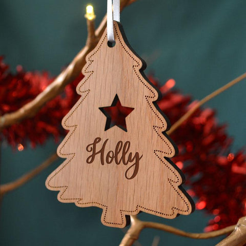 A personalised oak Christmas tree decoration which has been cut in a tree shape. The tree has a star and a name on the front.