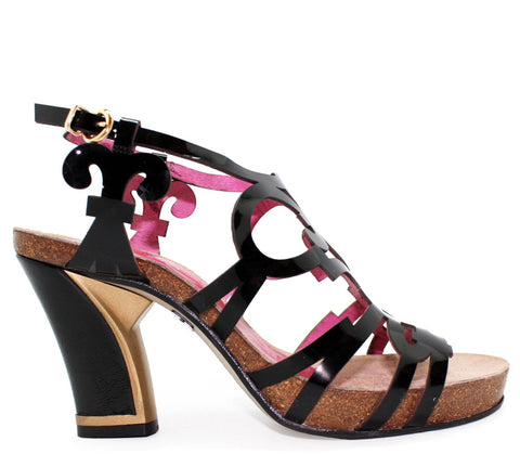 Leather heeled sandal with patent lazer cut pattern. Cork foot bed adds comfort and support all day long.