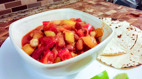 bowl of vegetable chili in bowl on plate with tortillas and limes