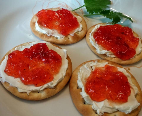 up close image of red pepper jelly on crackers with cream cheese