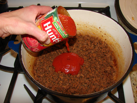 tomato sauce being added to pot of ground beef