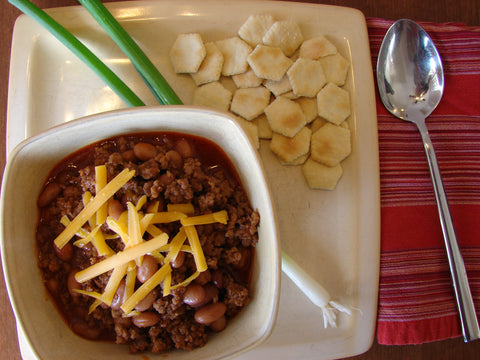 Bowl of chili on plate with crackers and cheese