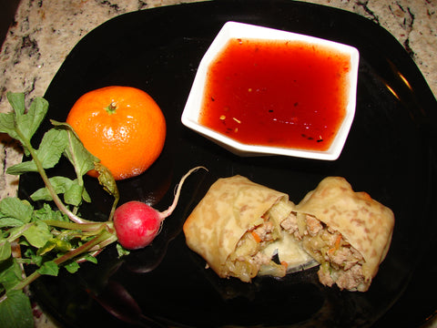 up close photo of red pepper jelly dipping sauce on plate with eggroll