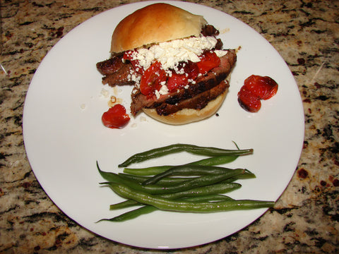 overhead photo of a steak sandwich on a plate with green beans