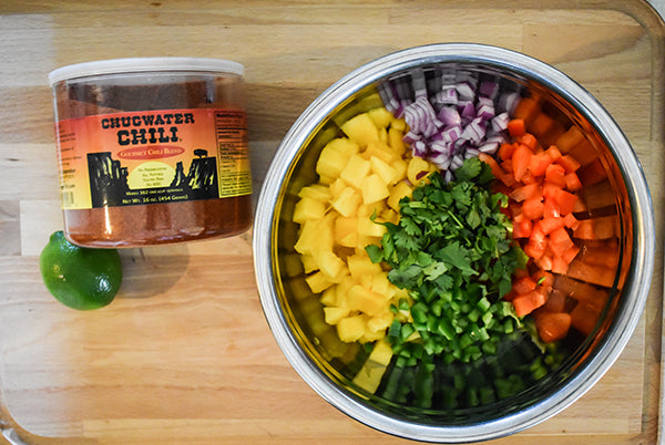 mango, bell peppers, red onion, jalapeno and cilantro in bowl beside chugwater chili seasoning and lime