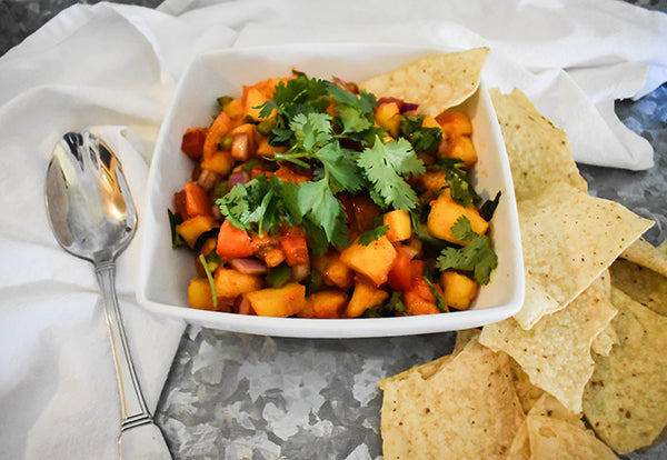 Mango salsa in bowl with chips and spoon